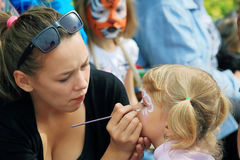 Makeup artist draws on the child's face mask tiger Stock Image
