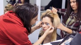 Professional make-up artist and hairdresser prepares actress to the stage. Makeup artist draws woman`s eyes with pencil. Hairdresser makes the hairstyle for stock video