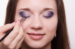 Makeup artist embellish eyelashes of a beautiful girl. Makeup artist paints the eyelids of a beautiful young girl in the makeup stock image