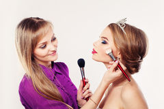 Makeup Artist Girl Applying Powder and Blush Stock Images