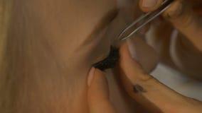 Makeup artist glues artificial eyelashes girl stock video footage