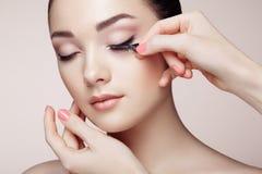 Makeup artist glues eyelashes royalty free stock photos
