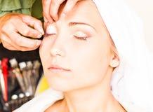 Makeup artist glues eyelashes. Beautiful woman Royalty Free Stock Photo
