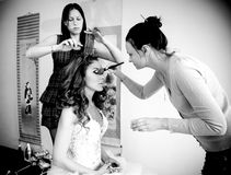 Makeup artist and hairdresser preparing bride for wedding Royalty Free Stock Photos
