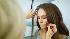 Makeup artist and hairstylist prepare model woman for fashion show slow motion. Makeup artist and hairstylist prepare model woman for fashion show in slow motion stock video