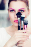 The makeup artist holds powder brushes Stock Image