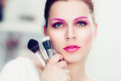 The makeup artist holds powder brushes. The makeup artist with bright pink make-up holds powder brushes. She touches with them a cheek. Studio portrait Stock Photos
