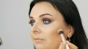 Makeup artist leads a woman in the face with a brush for applying powder, foundation or concealer. Lilac and pearly. Smoky eyes eyeshadow, eyes and face of stock video