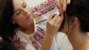 Makeup artist makes makeup of a beautiful brunette girl. stylist working on the image of the model. makeup artist draws eyes with. A pencil. 4k. 4k video stock video
