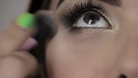 Makeup artist makes a girl beautiful makeup before an important event stock footage