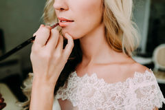 Makeup artist makes young beautiful bride bridal makeup. Morning preparation. Close-up hands near face. Makeup artist makes young beautiful bride bridal makeup stock images