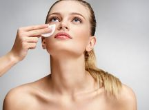 Makeup artist making the face cleaning with a cotton pad. Photo of beautiful woman with natural makeup on grey background. Skin care and beauty concept Stock Photo