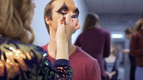 Makeup artist is making greasepaint to the actor in theatre. Make-up artist makes greasepaint on man`s face before his performance on scene. Professional worker stock footage