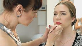 Makeup artist making make-up for stylish model stock footage