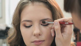 Makeup artist making make-up for a young model stock video footage