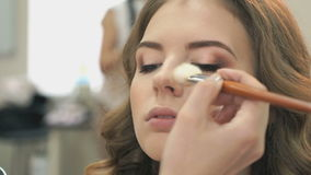 Makeup artist making make-up for young model stock video footage