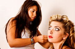 Makeup artist and model. Makeup artists refreshes model during shoot Stock Images