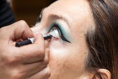 Makeup artist outlining white woman eyes. Close up of a makeup artist outlining white woman eyes Stock Image