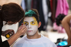Makeup Artist Paining Clown Face. Make up artist painting face of young clown Royalty Free Stock Photo
