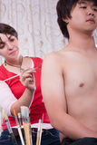 Makeup artist painting Asian boy. Makeup artist painting on body of Asian boy Royalty Free Stock Photography