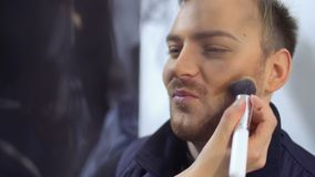Makeup artist paints cheeks of young man. Make-up artist makes a greasepaint on man`s face with brush. Woman paints his cheeks. Actor prepares to perform on the stock video footage