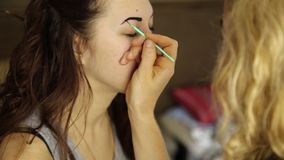 Makeup artist paints the eyebrows of a beautiful girl model using brush stock video