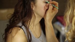Makeup artist paints the eyebrows of a beautiful girl model using brush stock video footage