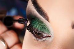 Makeup artist paints eyelashes Stock Photography