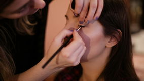 Makeup artist paints the eyes stock video