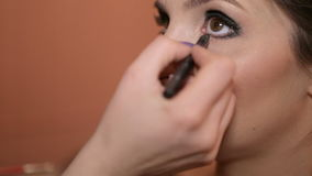 Makeup artist paints the eyes stock footage