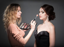 Makeup artist. Paints the face of a woman Royalty Free Stock Photo