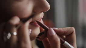 Makeup artist paints lips for girl. Professional make-up of model. Beautiful bride`s makeup. stock footage
