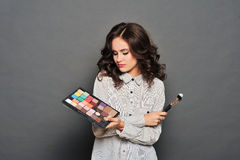 Makeup artist paints a very pretty brunette Stock Photography
