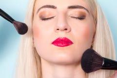Makeup artist paints a woman blush cheekbones. Makeup. Stock Photos