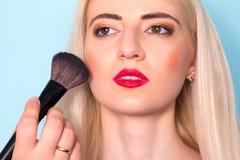 Makeup artist paints a woman blush cheekbones. Makeup. Stock Photo