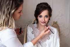 Makeup artist preparing beautiful bride before the wedding in a morning. Backstage beauty photo Royalty Free Stock Photos