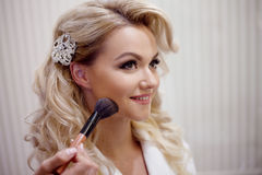 Makeup artist preparing bride before the wedding in a morning Royalty Free Stock Photos