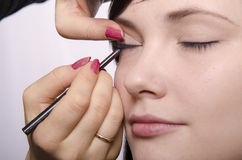 Makeup artist in the process of makeup colors eyelashes model Royalty Free Stock Image