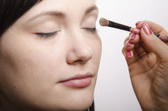 Makeup artist in the process of makeup colors upper eyelids model Royalty Free Stock Photos