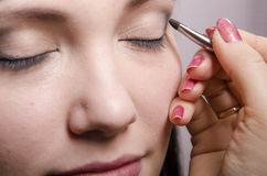 Makeup artist in the process of makeup colors upper eyelids model Royalty Free Stock Images