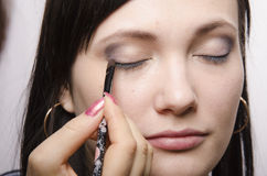 Makeup artist in the process of makeup colors upper eyelids model Royalty Free Stock Photography