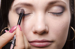 Makeup artist in the process of makeup colors upper eyelids model Stock Images