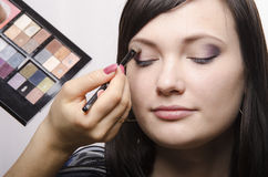 Makeup artist in the process of makeup colors upper eyelids model Stock Photography