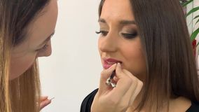 Makeup artist professionally applies lipstick on lips of a model with a beautiful face stock video footage