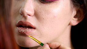Makeup artist puts confetti on lips. confetti on the lips, beautiful make up and bright colorer of lips.  stock video