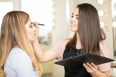Makeup artist putting on some eyeshadow. Beautiful young makeup artist applying some eyeshadow on a female customer in her beauty salon Stock Image