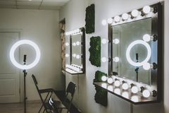 Makeup artist`s workplace a mirror with lamps on a white wall and a wooden armchair stock photography