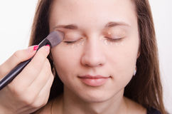 Makeup artist is shaded brush concealer on eyelids model Stock Image