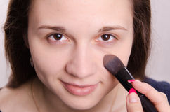 Makeup artist is shaded concealer brush on face model Royalty Free Stock Images