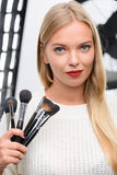 Makeup artist showing professional brushes. Makeup artist tools. Pleasant female makeup artist stands while presenting professional applying tools stock images